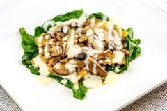 Włoski pierożek z świeżymi piec pieczarkami i śmietankowym parmesan serowym kumberlandem dekorował z szpinakiem na bielu talerzu zdjęcia royalty free