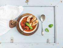 Włoski pomidoru, czosnku i basilu Pappa zupny al Pomodoro w metalu, rzuca kulą z chlebem na nieociosanej drewnianej desce nad bła Fotografia Royalty Free