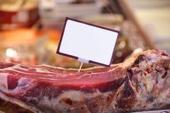 Włoski prosciutto cruto, sławny wieprzowiny mięso na shopwindow dla sprzedaży, uwędzony i farbujący Pustego papieru ceny karta Zdjęcie Stock