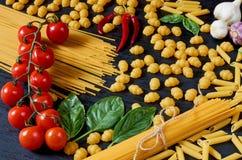 Włoski tradycyjny jedzenie, pikantność, składniki dla gotować, czereśniowi pomidory, chili pieprz, czosnek i różnorodny makaron,  fotografia royalty free