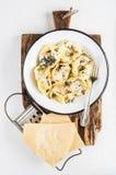 Włoskie tortellini Burro e szałwie z uwędzonym mięsem, masłem i mędrzec na nieociosanej drewnianej desce nad bielem, malowali tło Zdjęcie Stock