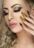 Włosy i makijażu temat: piękna dziewczyna z pięknym złotym gwozdziem w studiu Obrazy Royalty Free