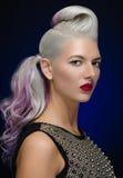 Włosy i makijażu temat: piękna młoda blond kobieta z kreatywnie włosianym tytułowaniem z czerwonymi wargami na zmroku - błękitny  obrazy stock