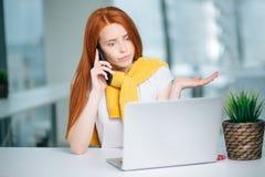 Wściekła kobieta jest ubranym kostium pracuje na linii używać mądrze telefon w biurku przy biurem Zdjęcia Royalty Free