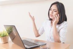 Wściekły bizneswoman jest ubranym kostium pracuje na linii używać mądrze Zdjęcia Stock