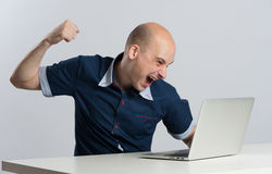 Wściekły mężczyzna wokoło uderzać pięścią jego laptop Obrazy Royalty Free