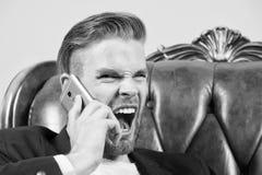 wściekły szef Mężczyzna krzyka telefonu komórkowego dobrze przygotowywający agresywnie popielaty tło Biznesmena gniewny wywoławcz zdjęcia stock