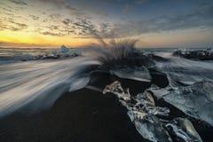 Wściekać się macha niszczących lodowych bloki przy wschód słońca na diament plaży zdjęcie stock