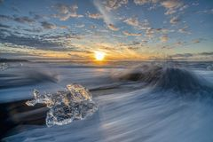 Wściekać się macha niszczących lodowych bloki przy wschód słońca na diament plaży zdjęcie royalty free