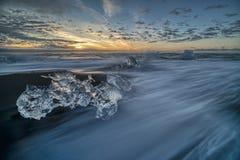 Wściekać się macha niszczących lodowych bloki przy wschód słońca na diament plaży fotografia stock
