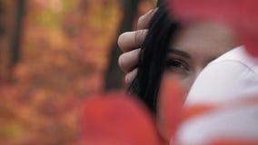 Wśród czerwieni jesień liście są ciemnowłosym kobietą w rękach mężczyzna i spojrzenia w odległość, zwolnione tempo zbiory wideo
