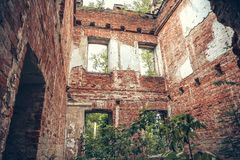 Wśrodku rujnującej, zaniechanej antycznej cegły, starzał się grodowego budynek przerastającego z trawą i roślinami obrazy royalty free