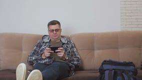 W średnim wieku mężczyzny obsiadanie na kanapie w mieszkaniu lub pokoju hotelowym używa internet w smartphone, obok on jest a zbiory