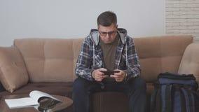 W średnim wieku mężczyzny obsiadanie na kanapie w mieszkaniu lub pokoju hotelowym używa internet w smartphone, obok on jest a zdjęcie wideo
