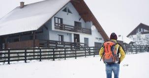 W śnieżnym zima dnia turystycznym mężczyźnie z dużą turystyczną torbą w jego tylny przyjeżdżający jego miejsce przeznaczenia haln zbiory wideo