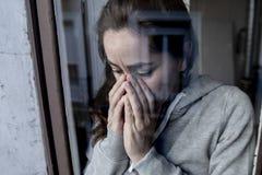 W średnim wieku łacińskiej kobiety smutny i przygnębiony patrzeć przez nadokiennego refection w depresji pojęciu zdjęcie royalty free