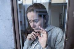 W średnim wieku łacińskiej kobiety smutny i przygnębiony patrzeć przez nadokiennego refection w depresji pojęciu fotografia stock