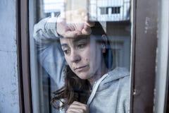 W średnim wieku łacińskiej kobiety smutny i przygnębiony patrzeć przez nadokiennego refection w depresji pojęciu zdjęcie stock