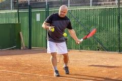 W średnim wieku łysy mężczyzna bawić się tenisa na plenerowym sądzie s?oneczny dzie? obraz stock