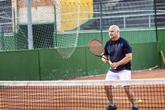 W średnim wieku łysy mężczyzna bawić się tenisa na plenerowym sądzie s?oneczny dzie? obraz royalty free