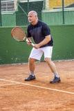 W średnim wieku łysy mężczyzna bawić się tenisa na plenerowym sądzie s?oneczny dzie? zdjęcia stock