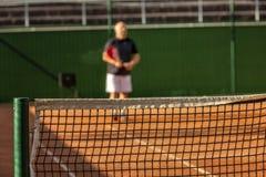W średnim wieku łysy mężczyzna bawić się tenisa na plenerowym sądzie s?oneczny dzie? plama obrazy royalty free