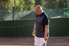 W średnim wieku łysy mężczyzna emocjonalnie bawić się tenisa na sądzie Gubi przeciwnika plenerowy fotografia royalty free