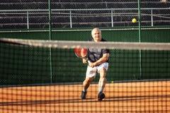 W średnim wieku łysy mężczyzna emocjonalnie bawić się tenisa na sądzie plenerowy zdjęcia royalty free