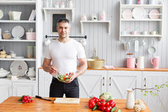 W średnim wieku atleta, trzyma puchar talerz z przygotowaną sałatką ogórek i pomidor Jarski jedzenie Fotografia Stock