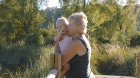 W średnim wieku babcia trzyma jej blondynki dziewczynki pozycję na drewnianym moscie w naturalnym parku zbiory