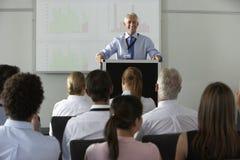 W Średnim Wieku biznesmen Dostarcza prezentację Przy konferencją Zdjęcia Royalty Free