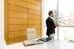 W średnim wieku biznesmen ma coffe przerwę w nowożytnym biurze Fotografia Royalty Free