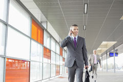W średnim wieku biznesmen na wezwaniu podczas gdy chodzący w linii kolejowej staci Fotografia Royalty Free