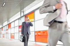 W średnim wieku biznesmen na wezwaniu podczas gdy chodzący w linii kolejowej staci Fotografia Stock
