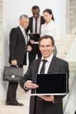 W średnim wieku biznesowy mężczyzna używa laptop z kierownictwami w bac Obraz Stock