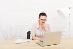 W średnim wieku bizneswoman w biurze z laptopem zdjęcia stock