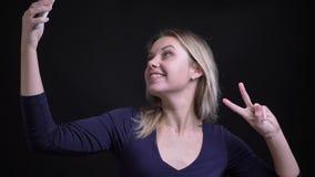W średnim wieku blondynka bizneswoman robi fotografiom smilingly gestykuluje kawałka znaka na smartphone na czarnym tle zbiory