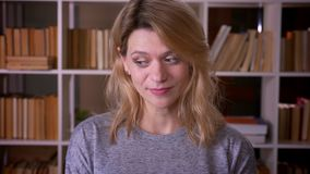 W średnim wieku blondynka nauczyciel ono uśmiecha się shyly w kamerę niezwykle zawtydza przy biblioteką zdjęcie wideo