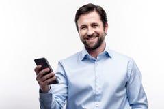 W średnim wieku brodaty mężczyzna pozuje z jego telefonem komórkowym zdjęcia royalty free