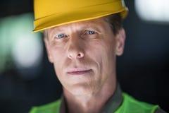 W średnim wieku budowniczy patrzeje kamerę w ciężkim kapeluszu zdjęcie royalty free