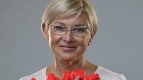 W średnim wieku dama cieszy się perfumowanie tulipany, powitania na Macierzystym dniu, rocznica zbiory