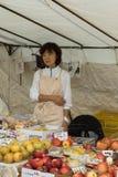 W średnim wieku Japoński żeński sprzedawca sprzedaje jabłka Fotografia Stock