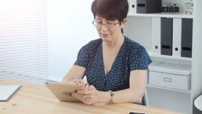 W średnim wieku kobieta w biurze używać pastylkę zbiory wideo