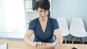 W średnim wieku kobieta w biurze używać pastylkę zdjęcie wideo
