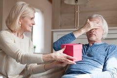 W średnim wieku kobieta daje teraźniejszości mężczyzna zdjęcia stock