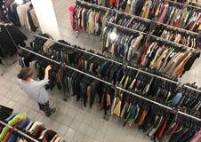 W średnim wieku kobieta kupuje odzieżowego przy drugi ręki sklepem Zdjęcia Stock