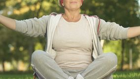 W średnim wieku kobieta medytuje w parku, oddychający ćwiczenie, relaksuje po treningu zdjęcie wideo