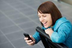 W średnim wieku kobieta ono uśmiecha się przy telefonem komórkowym Zdjęcia Royalty Free