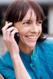 W średnim wieku kobieta ono uśmiecha się z telefonem komórkowym Fotografia Stock