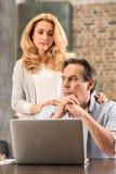 W średnim wieku kobieta patrzeje wzburzonego męża używa laptop w domu Obrazy Stock